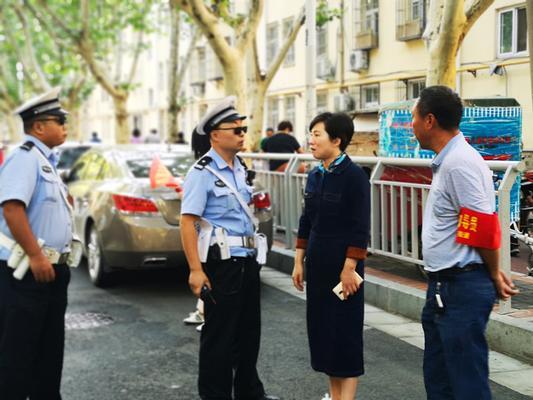 市实验幼儿园园长郝江玉与交警、社区工作人员沟通交通疏导情况